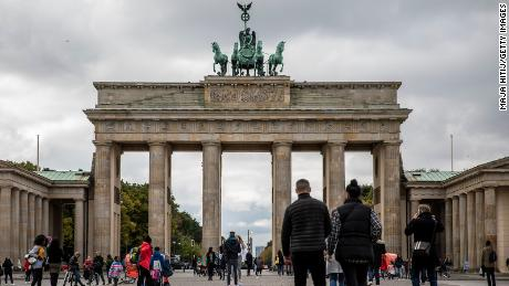 Tourists march at the Brandenburg Gate in Berlin, Germany on October 12, as gatherings were limited to 10 people and an 23-hour curfew imposed in several areas.