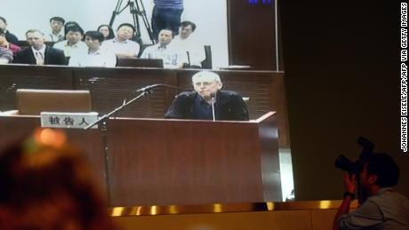 Journalists follow the progress on a television screen of the trial of British investigator Peter Humphrey (center) linked to beleaguered pharmaceutical giant GSK and his wife, at the Shanghai Intermediate Court on August 8, 2014.
