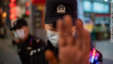 A police officer wears a face mask as a preventive measure against coronavirus. Harper was arrested near the start of the pandemic and would not learn about it for weeks.