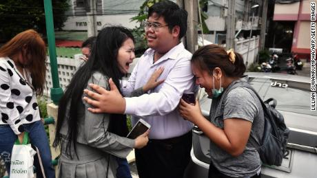 """Pro-democracy activist Bunkueanun """"Francis"""" Paothong comforts loved ones before he enters the Dusit police station to answer charges of harming Thailand's Queen Suthida on October 16, 2020."""