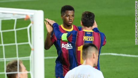 Ansu Fati celebrates with  Lionel Messi after scoring a goal during the UEFA Champions League football match between FC Barcelona and Ferencvarosi TC at the Camp Nou stadium on Tuesday.