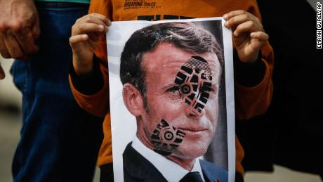 A child holds a photograph of Emmanuel Macron, stamped with a shoe mark, during a protest against France in Istanbul on October 25