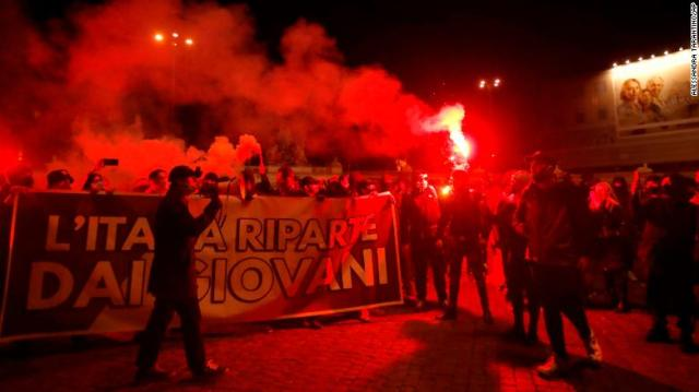People light flares as they protest against measures to curb the spread of Covid-19, in Rome, Italy on Tuesday.