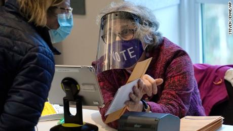 A well-protected poll worker in Newton, Mass., cuts down on the risk of voting. Do your part by wearing a mask and social distancing.