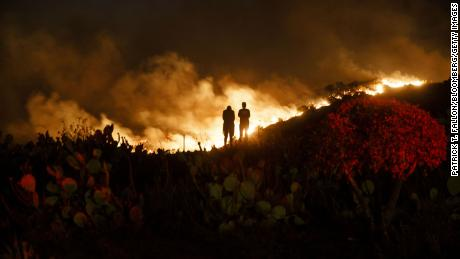 People watch from a hillside during the Silverado Fire in Lake Forest, California, on Monday, Oct. 26, 2020.
