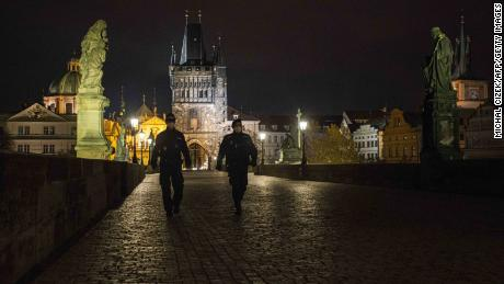 Police officers walk across the empty Charles Bridge in Prague during the night-time curfew imposed by the Czech government on October 28.