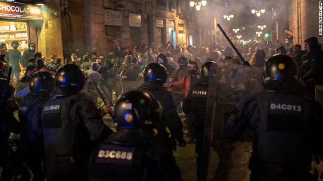 Police clash with anti-lockdown protesters in downtown Barcelona, Spain, on Friday.