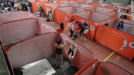 ผู้อยู่อาศัยในศูนย์อพยพเนื่องจากฝนเริ่มตกในกรุงมะนิลาประเทศฟิลิปปินส์ในวันอาทิตย์