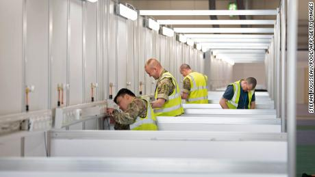 Members of the military and private contractors help to transform the ExCel centre in London into an NHS Nightingale Hospital for coronavirus patients, on March 30, 2020.