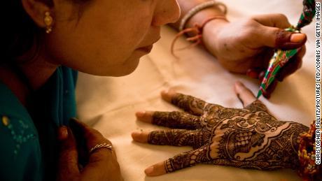ศิลปินใช้เฮนน่ากับมือของเจ้าสาวสาวชาวอินเดีย
