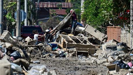 People attempt to retrieve their belongings amid the mud after Hurricane Eta hit as they prepare to evacuate the Omonita neighborhood in El Progreso, Yoro Department, Honduras.