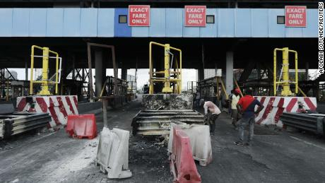 Workers clean up the Lekki toll gate, a site where soldiers had opened fire on protesters late on October 20, 2020