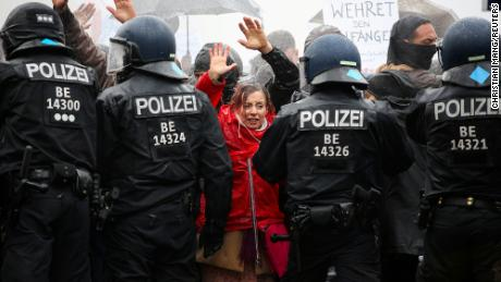 Demonstrators put up their hands in front of police officers during a protest against the government's coronavirus restrictions in Berlin, November 18, 2020.
