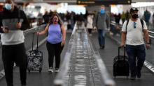 Travelers at Denver International Airport on Friday. More than 1 million people were screened by TSA at US airports on Friday despite warnings urging people not to travel due to rising Covid-19 cases.