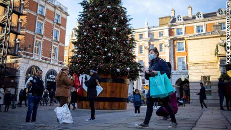 Pedestrians walk behind a Christmas tree in Covent Garden, central London, on November 22, 2020.
