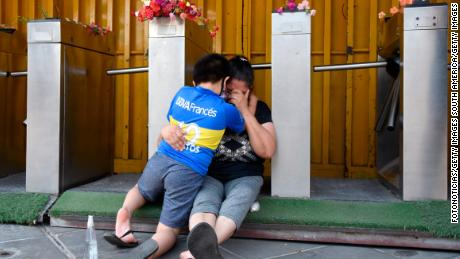 Fans of Boca Juniors cry and hug eachother near La Bombonera.