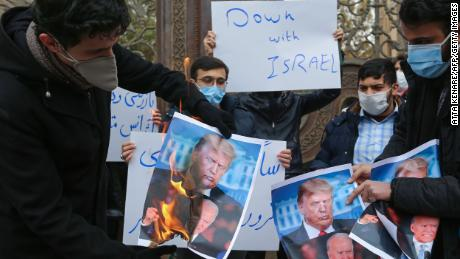 Students of Iran's Basij paramilitary force burn posters depicting Donald Trump and Joe Biden during at the foreign ministry in Tehran, on November 28, 2020, to protest the killing of prominent nuclear scientist Mohsen Fakhrizadeh a day earlier near the capital.
