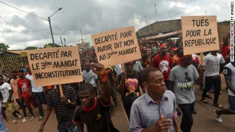 """Protesters hold signs to read """"Beheaded for saying no to the unconstitutional third term"""" and """"Killed for the republic"""" during a march to denounce the deaths of protesters killed in poll-related violence, in central-eastern Daoukro, on Nov. 21."""
