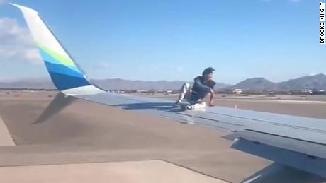 An image from video shot by a passengers shows the man sitting on the wing of the Alaska Airlines jetliner.