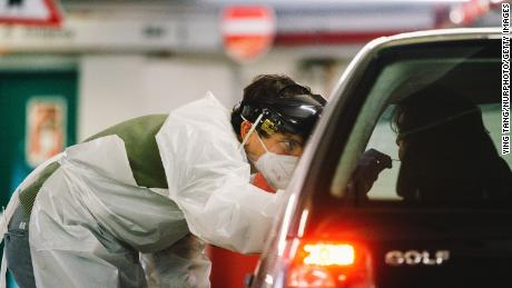 On December 14, medical staff administer antigen tests at the parking lot of the Lanxess Arena in Cologne, Germany.