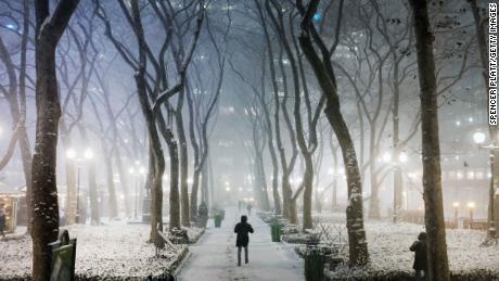 People walk through Manhattan in a snow storm on December 16, 2020 in New York City