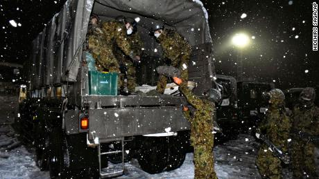 Japan Self-Defense Forces personnel prepare food and water for people stuck on Kanetsu expressway on December 17.