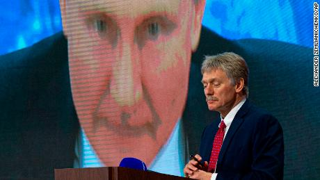 Kremlin spokesman Dmitry Peskov looks on as Russian President Vladimir Putin speaks via video at a news conference. Both have blamed Western intelligence agenices for being involved with Navalny.