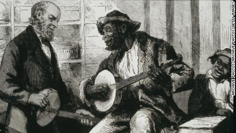 A Black man plays a banjo for White listeners in the 1880s United States.