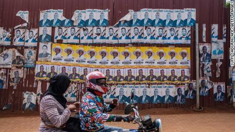 Posters of incumbent President Yoweri Museveni (yellow) and Bobi Wine are seen along a street in Kampala on January 6