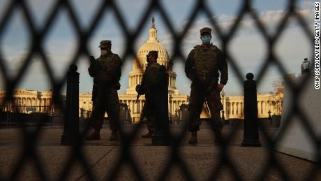 Members of the New York National Guard stand guard along the fence that surrounds the Capitol.