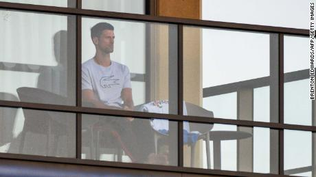 Men's singles world number one tennis player Novak Djokovic of Serbia sits on his hotel balcony in Adelaide, Australia, on January 18, one of the locations where players have quarantined for two weeks upon their arrival ahead of the Australian Open tennis tournament in Melbourne.