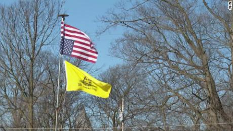 """An upside-down Stars and Strips and a """"Don't Tread on Me"""" Gadsden flag suggest anti-government feeling in Woodstock, Ohio."""