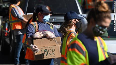 Volunteers load free groceries into cars for people experiencing food insecurity due to the pandemic, December 1, 2020, in LA. Helping other people within your community is a form of spiritual rest.