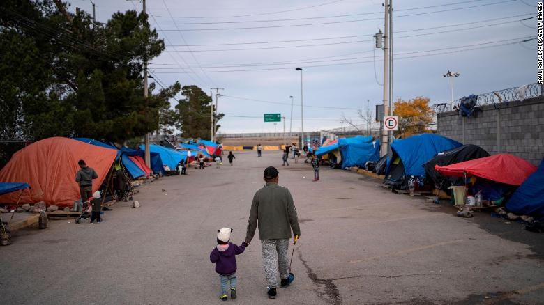 In this December 11, 2019, file photo, a man walks with his daughter at an asylum seekers camp near the Zaragoza bridge in Ciudad Juarez, Mexico.