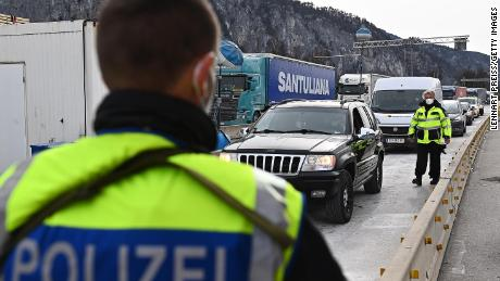 A policeman stands as a guard in an Austrian boarder as a queue of cars enter Germany.