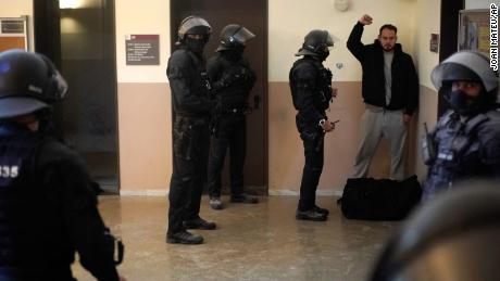 The rapper reacts next to police officers before being taken into custody on Tuesday.