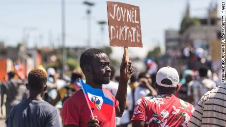 People hold up signs during a demonstration on February 14, 2021 in  Port-au-Prince.