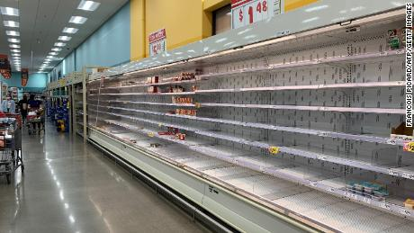 Shoppers are seen wandering next to near-empty shelves in a supermarket in Houston, Texas on February 20, 2021