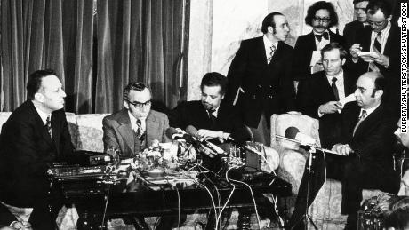 Oil ministers including Ahmed Zaki Yamani (seated, mustache and beard) announce that OPEC will lift the oil embargo against the United States.
