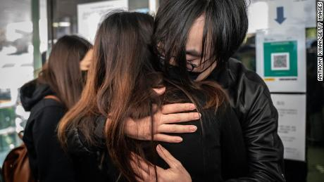 Mike Lam King-nam, who participated in the pro-democracy primaries, gives his wife a hug before reporting to the Ma On Shan Police Station on February 28 in Hong Kong.