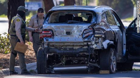 Los Angeles County Sheriff deputies gather evidence from the car Tiger Woods was driving when he seriously injured on February 23, 2021 in Rolling Hills Estates, California