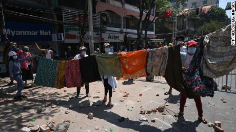 Women hang a collection of longyi, a traditional clothing widely worn in Myanmar, across a road during a demonstration against the military coup in Yangon on March 8.