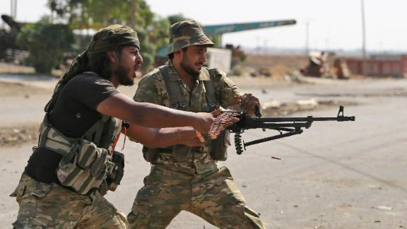 Turkish-backed Syrian fighters take part in a battle in Syria's northeastern town of Ras al-Ain as Turkey and its allies continue their assault on Kurdish-held border towns in northeastern Syria on October 14, 2019.