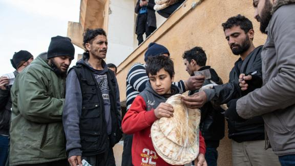 A displaced boy carries a bag of bread as people queue for food distributed by a nonprofit in Idlib on February 19, 2020.