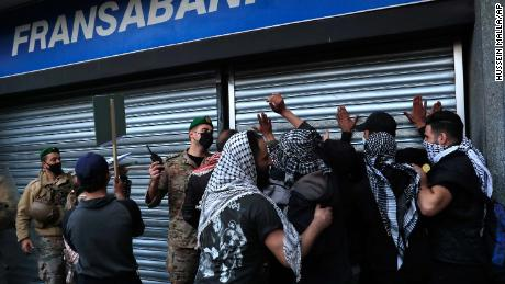 An army officer pushes back protesters who tried to break down a bank door during a protest demanding that local banks allow people to withdraw their money on February 26.