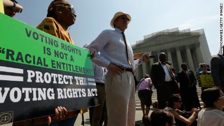 Supporters of the Voting Rights Act listen to speakers discussing rulings outside the US Supreme Court building on June 25, 2013 in Washington.