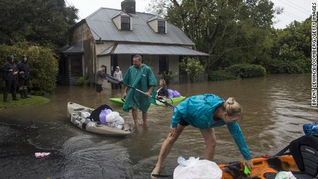 Residents unload household items from kayaks at a street submerged in floodwaters in Windsor, New South Wales, Australia, on March 22.