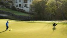 McIlroy lines up a putt on the fourth green in his match against Poulter.
