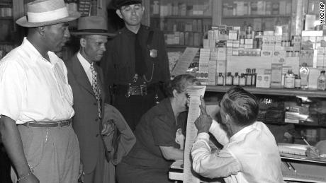 An election official tells World War II veteran Lewis K. McGuire, left, and physician S. M. Lewis, right -- who tried to vote in 1945 in Atlanta -- that the primary is for White people only.