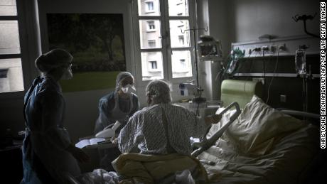 Nurses help a Covid-19 patient at a Paris hospital on March 18.